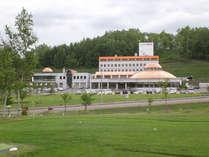*【外観(夏)】豊かな自然に包まれた桜岡湖のほとりに位置する当館。