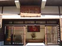 玄関正面では八方睨みの≪達磨大使≫がお迎えします。肖像画の巨匠「馬掘喜孝画伯」の作品です。