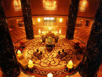 ダーク・ワインレッドの大理石の柱と、壁面を飾る鮮やかな絵画が、壮麗なミュージアムを彷彿させるロビー。