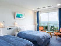 窓の外からは、エメラルドグリーンの海と美しい青空が一望できる、開放的なお部屋です。
