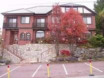 木々の紅葉にレンガ造りが映えるホテル