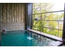 男女別活性石人工温泉大浴場。窓からは、緑が見えて開放的です