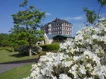 新緑と白のつつじのコントラストが美しいホテル外観