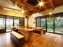 【食事処】屋久島の杉で作られたテーブル。窓からは晴天の日には森の向こうに太平洋が見えます。