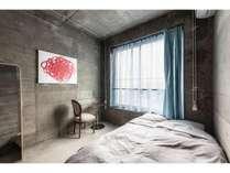 コンクリートに包まれた静かなダブルベッドのお部屋。