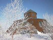 きらめく冬の朝樹氷越しに施設を望む。