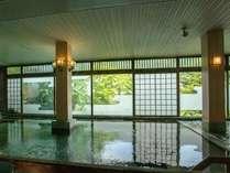 本館の大浴場。目線に広がる緑と露天風呂から川音を楽しめる。お部屋からの移動でご不便をおかけ致します。