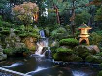 【1F:ロビー庭園】季節の花々と滝の流れが安らぎのひと時を演出します。