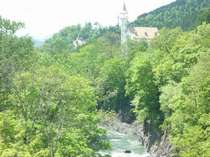 【錦仙峡から眺めるホテル】初夏の新緑の中にたたずむホテル渓谷