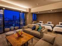 リビングルーム(夕方から夜への雰囲気)。ゆったりしたソファーセット、団らんのひと時をお楽しみ下さい。