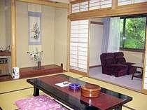 和室10畳の客室例。窓の外には緑が広がり、癒されます