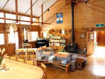 薪ストーブのあるホールには、タモ材の大きな食事用テーブル、ゆったりとしたソファ、ピアノがあります。