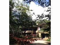少し色づいた木々に囲まれた秋晴れのホテル外観