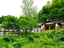 *夏は美しい新緑に囲まれる当館(外観)