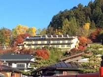 秋、中橋より望む城山の紅葉に囲まれる当館