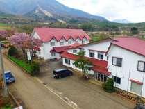 雄大な飯縄山をバックに、桜や新芽が輝く春。赤い屋根の大きな建物が目印です。