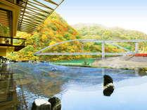 秋の紅葉に囲まれた柏屋自慢の露天風呂。電車が通る時刻に合わせてご入浴されるお客様も。