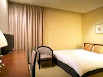 ゆったりとしたベッドを備え、落ち着きのあるダブルルーム(一例)