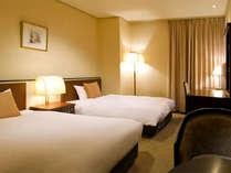 デスクも備えたシンプルなツインルーム(一例)。全室にシモンズ社製のベッドを導入。