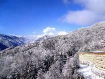 【冬のホテル外観】雪をまとった北アルプスを望むロケーション