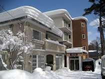 青空と白い雪の中に佇むブラウニーコンドミニアム