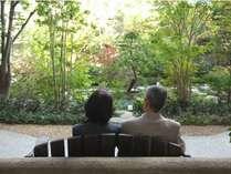 【1階 中庭】手入れが行き届いた庭園は、季節の花々が美しい。木製のベンチで心地よい時間を。