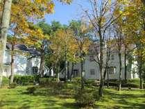 コテージ外観。木立を縫って立ち並ぶ18棟72室の白いコテージ。全室暖炉付リビングのある広々客室。