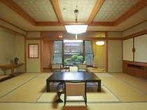 池を泳ぐ鯉、日本庭園を目の前にした次の間付きの特別室。