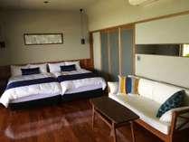 チィーク材の床にチィーク材のソファ。サータ社のセミダブルベッド。