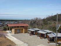 キャンプエリアから見たコテージ全景、建物の向こうは日本海佐渡夕日が一望!