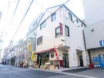 白い外観に臙脂の色が似あう3階建て。チェックインは2階です。