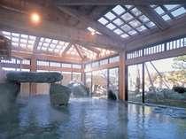 湯舟に巨石を配した野趣おふれる大浴場。自然の光を採り入れることによって開放感をUPさせる。