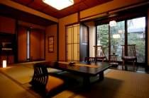 露天付き客室一例 御形。飛騨家具のチェアに座り、庭園を臨む。